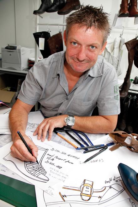 Martin Lenz savo kabinete, pilname eskizų ir avalynės prototipų